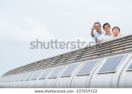 Asian grandfather, father and son standing on the bridge - stock photo