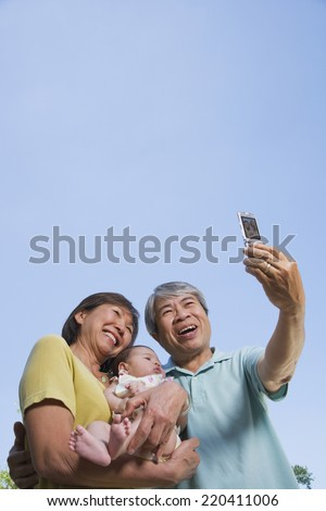 Asian grandparents holding baby grandchild and taking photograph - stock photo