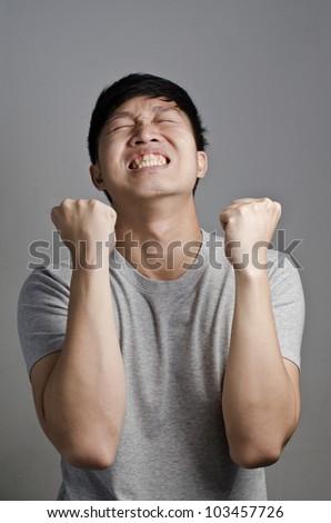 Asian guy doing win face - stock photo