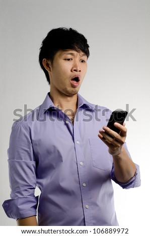 Asian guy get shocked by his smart phone - stock photo