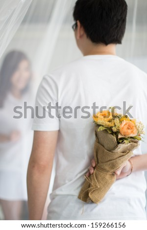 Asian guy holding flower behind him trying to surprise his waiting girl friend - stock photo