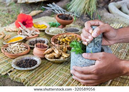 Asian hands preparing ayurvedic medicine with granite mortar and pestle.  - stock photo