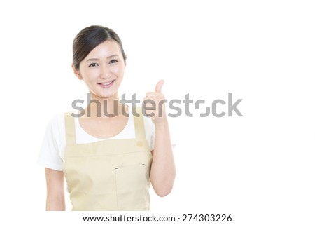 Asian housewife showing thumbs up sign - stock photo