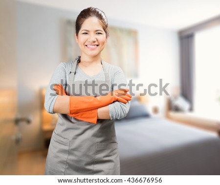 asian housewife wearing rubber gloves crossed arms - stock photo