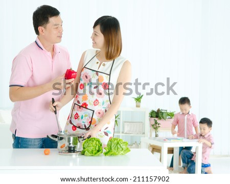 Asian husband and wife cooking in the kitchen and kids are doing schoolwork in the living room - stock photo