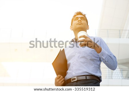 Asian Indian business man hand holding take away hot coffee cup and file folder in morning sunlight, outdoors modern office business concept. - stock photo