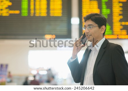 Asian Indian Business man on the phone during his business travel, at the airport . - stock photo