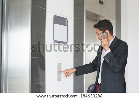 Asian Indian businessman pressing on elevator button, waiting door open to enter inside the lift. - stock photo