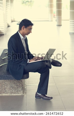 Asian Indian businessman using laptop computer while waiting train at railway station. - stock photo