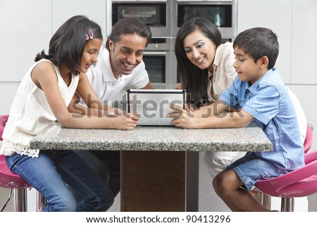 Asian Indian family husband & wife, children, girl and boy, using tablet computer in the kitchen at home