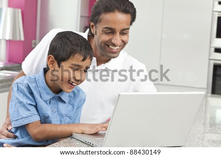 Asian Indian father and son, man and boy, using laptop computer in the kitchen at home