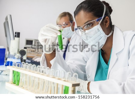 Asian Indian female medical or scientific researcher or doctor looking at a test tube of green solution in a laboratory with her caucasian colleague - stock photo