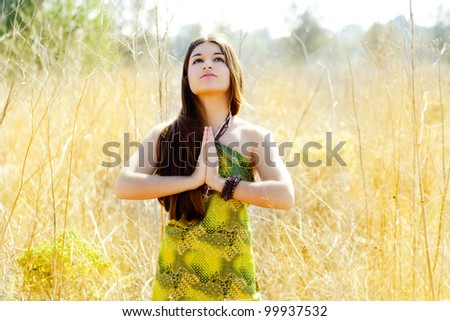 Asian indian woman praying hands  in golden field with green dress - stock photo