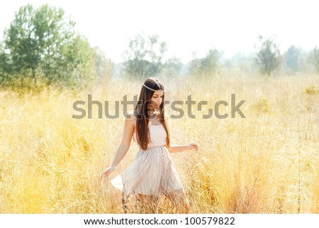 Asian indian woman walking in golden dried grass field - stock photo