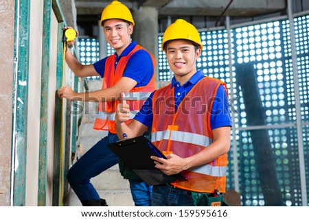Asian Indonesian builder or craftsman and supervisor with hardhats, checklist and measure tape controlling or checking a wall of a tower building or construction site