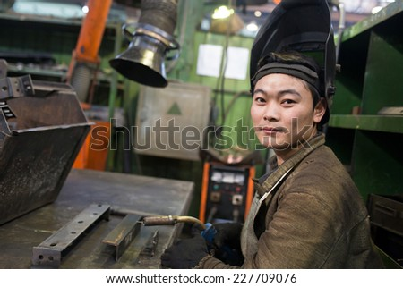 Asian industrial welder worker at factory workshop background  - stock photo