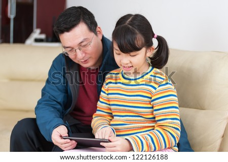 Asian kid and her father using a digital tablet at home