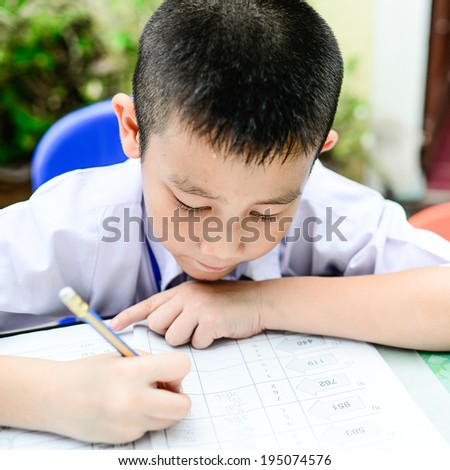 Asian kid do home work in classroom - stock photo