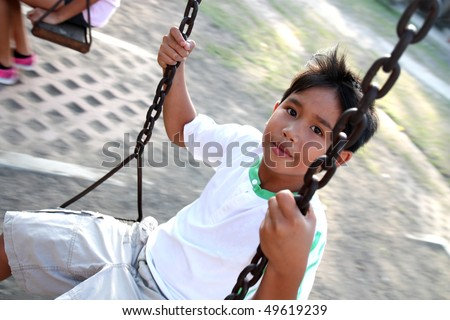 asian kid enjoying a swing ride - stock photo