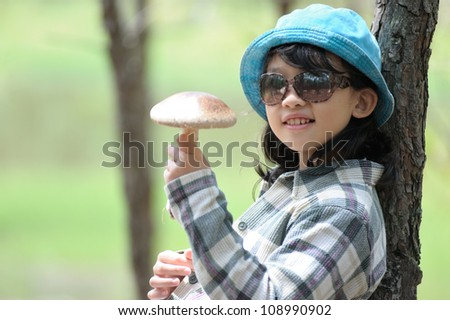 Asian kid holding a mushroom and sitting against a tree - stock photo