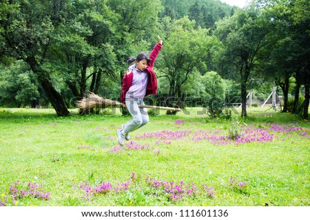Asian kid jumping on the meadow  in rural area of Shangri-La county,Yunnan province, China - stock photo