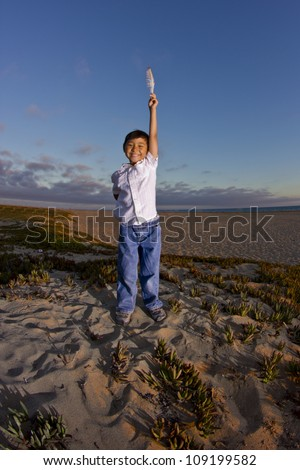 asian kid on the beach holding a feather