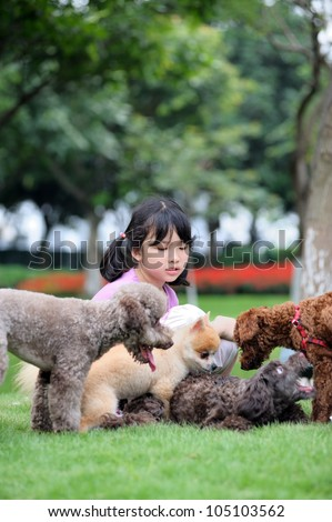 Asian kid sitting and playing with group of dogs on the lawn - stock photo
