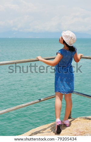 Asian kid standing on the shore - stock photo
