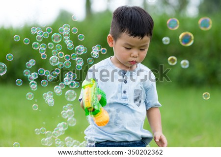 Asian kid use of the bubble blower