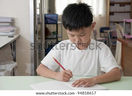 Asian kid writes on notebook in classroom - stock photo
