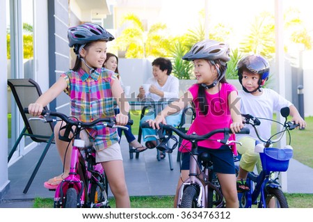 Asian kids enjoying cycling - stock photo