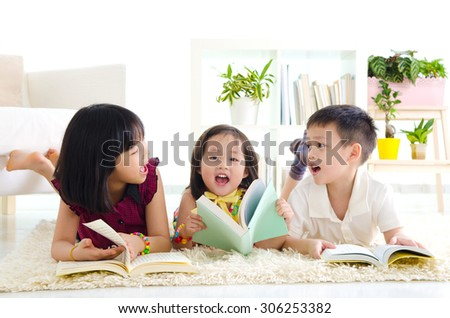 Asian kids lying on the carpet and reading
