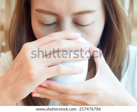 Asian lady drink a cup of tea - stock photo