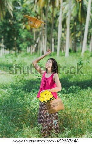 Asian lady in traditional style costume. Happy funny and enjoy lifestyle in coconut palm garden during daylight.