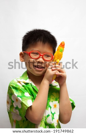 Asian little boy playing water gun