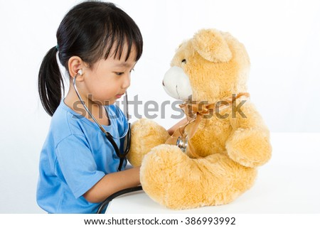 Asian Little Chinese Girl Playing Doctor with Teddy Bear isolated on white background - stock photo