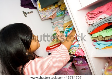asian little girl arranging her clothes collection in the closet - stock photo