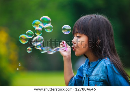 Asian little girl is blowing a soap bubbles, Outdoor Portrait - stock photo