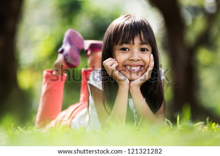 Asian little girl laying on green ground - stock photo