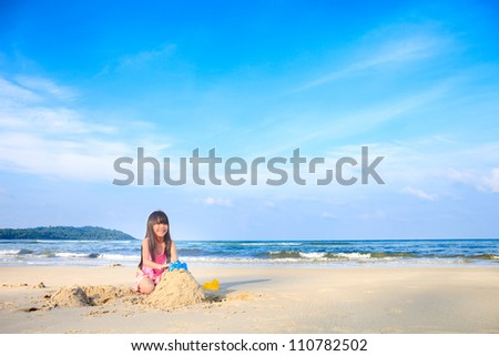 Asian little girl playing sand on the beach - stock photo