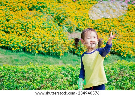 Asian little girl playing with bubbles in floral background