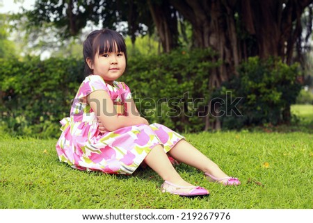 asian little girl reading a book in the park. - stock photo