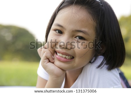 Asian little girl relax and smiling happily in the park