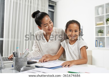 Asian little girl sitting at workplace of her mother - stock photo