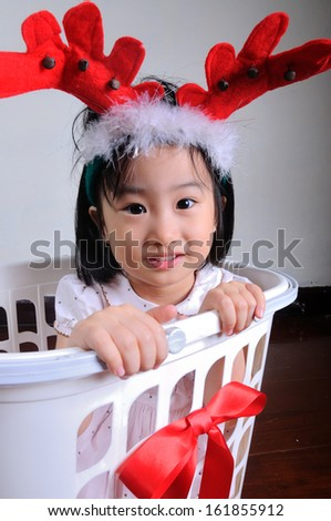 asian little girl wearing a reindeer headband in gift basket, Christmastime, New Year holiday concept