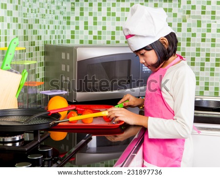 Asian Little Girl with chef dress slicing fruits in kitchen