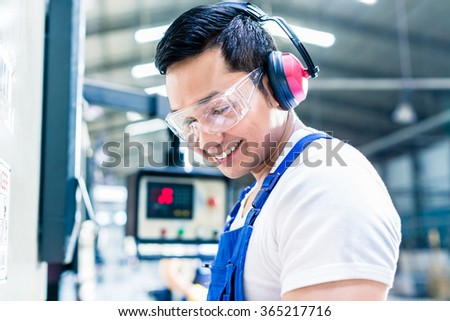 Asian machine operator in production plant checking data  - stock photo