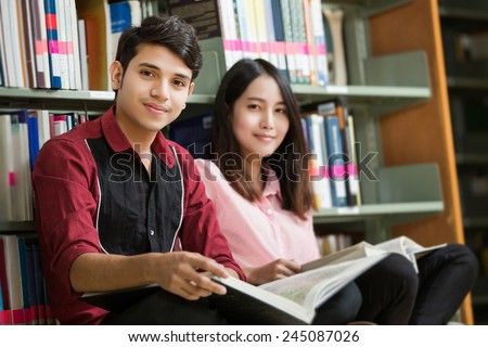 Asian male and female students reading at the library. The bookshelf - stock photo
