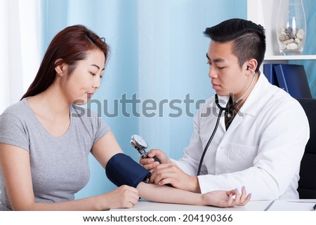 Asian male doctor taking blood pressure of a female patient - stock photo