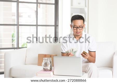 asian male enjoying cash back credit card - stock photo
